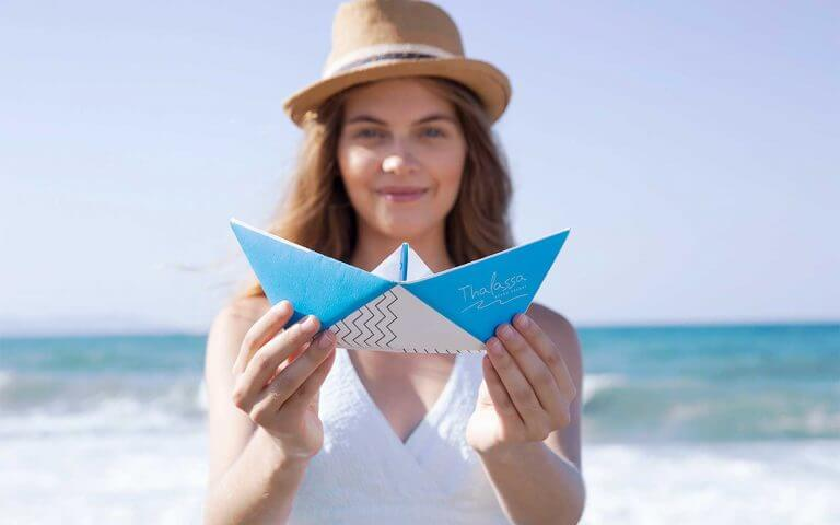 Woman holding origami ship with thalassa logo