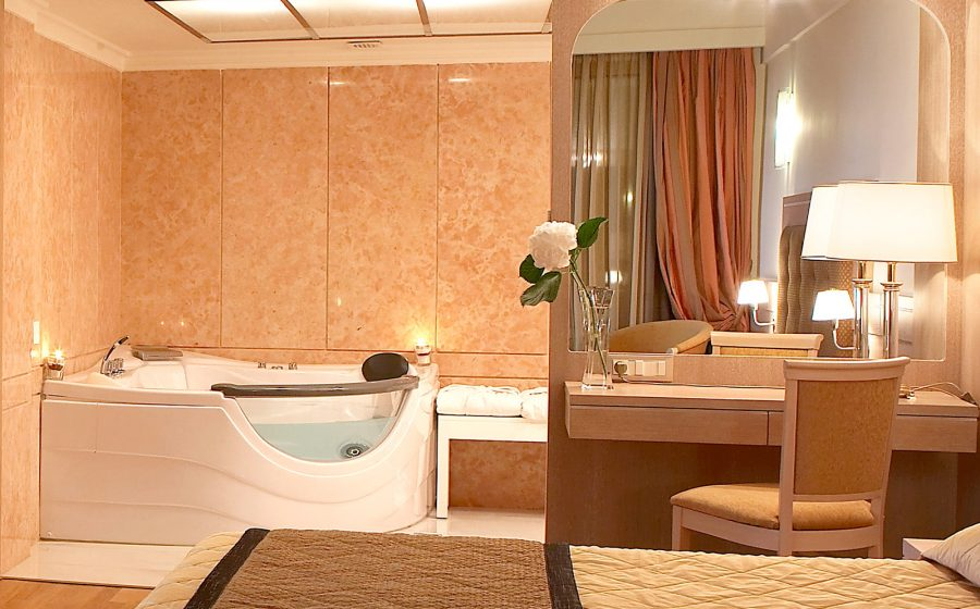 Bath, bed and bedside table of a superior suite
