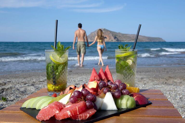 Couple walking along the seaside leaving drinks and fruit on table