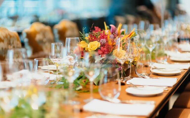 Flowers, glasses, dishes and towels on table