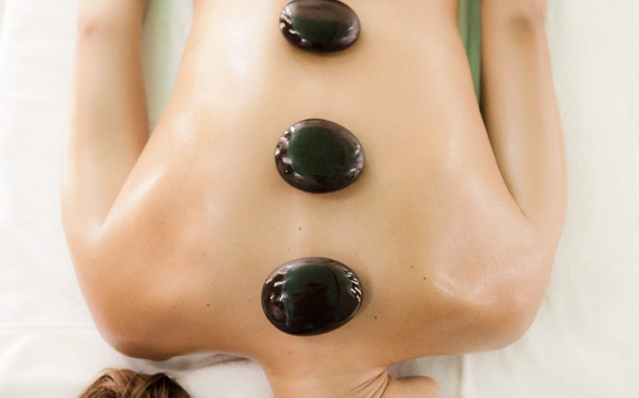 Therapeutic stones on woman laying in bed
