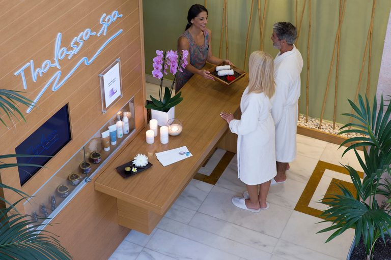 Staff of the spa reception offering towels to couple