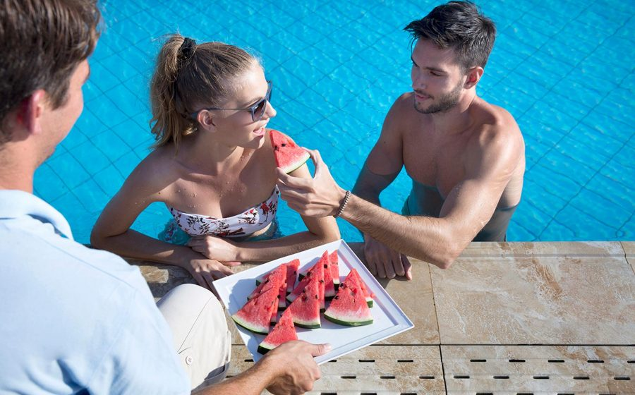 Couple in pool having watermelon served