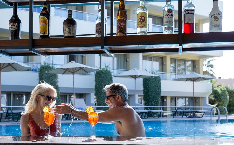 Playfull couple having drinks at the pool bar
