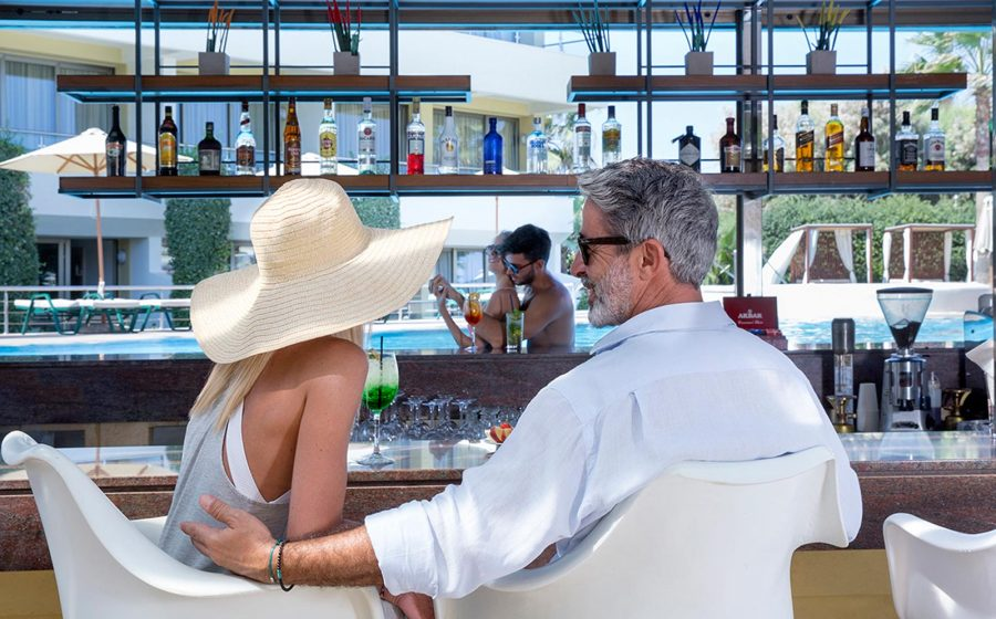 Couples relaxing by the pool bar