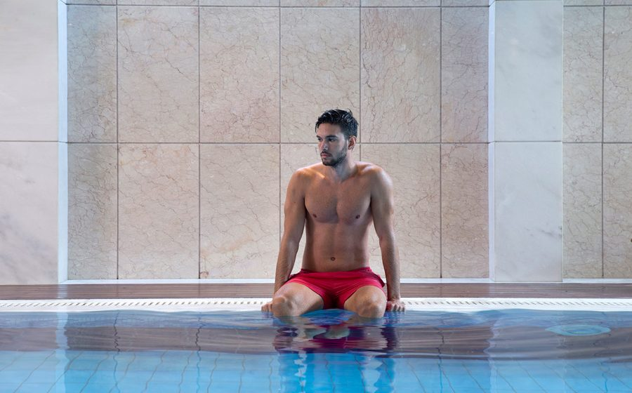 Jeune homme dans la piscine spa