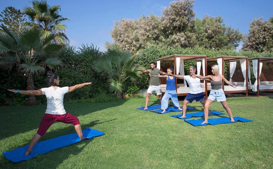 Two couples taking yoga class from instructor outdoors