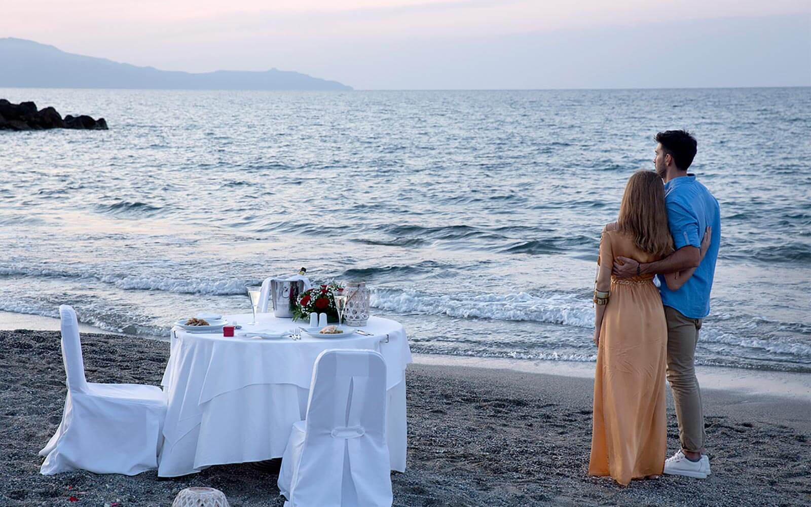 Couple watching the sunset near a table by the sea