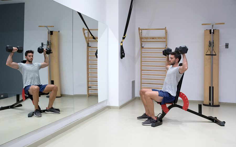 man pressing dumbbells looking at mirror